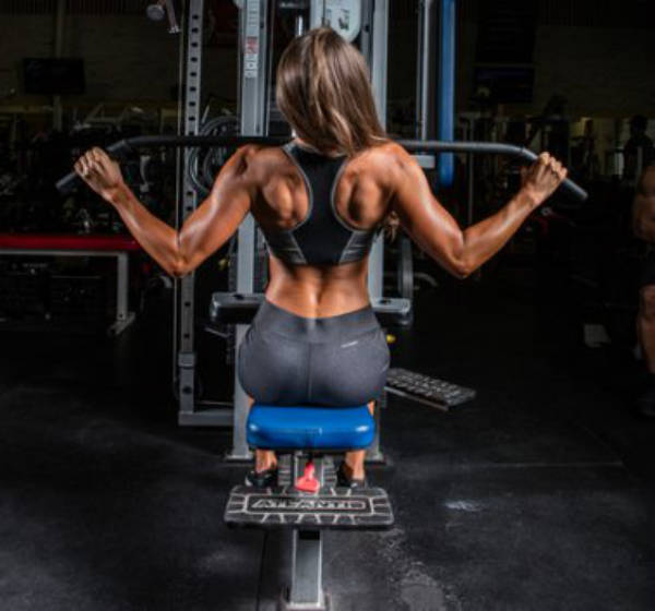 Taylor Chamberlain completing a lateral pull down, showing her pumped lats, toned delts and glutes