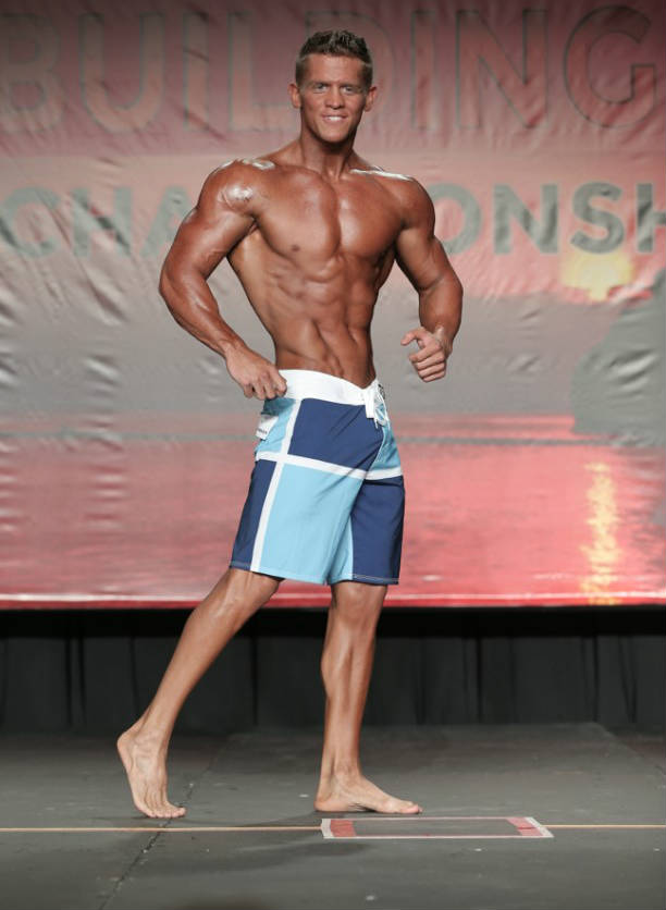 Tyler Stines competing at a mens physique competition showing off his ripepd abs and large delts and arms