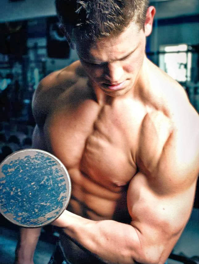 Tyler Stines completing a bicep curl, looking down at his bulging bicep