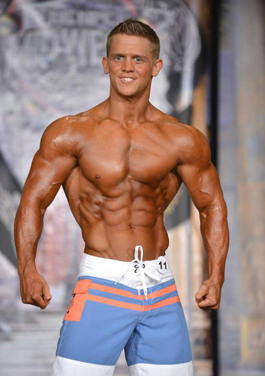 Tyler Stines posing at a physique competition, showing his ripepd abs, obliques and large delts and biceps
