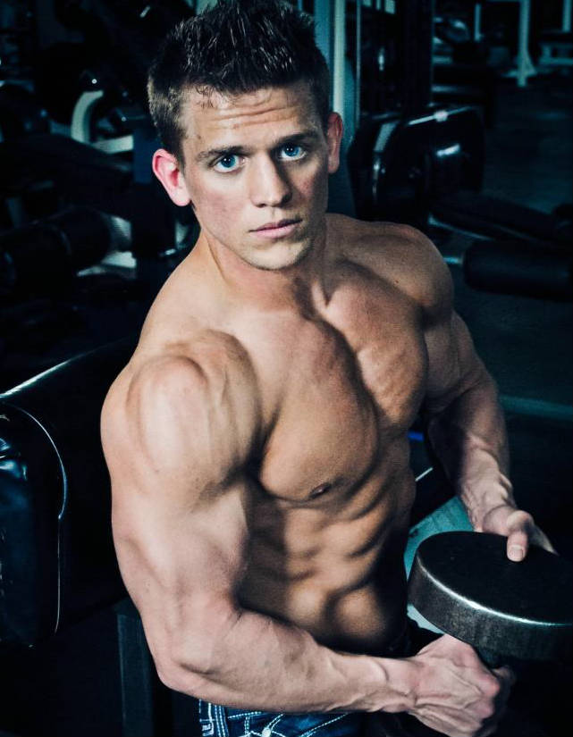 Tyler Stines holding a dumbbell, showing off his large arms, chest and ripped abs