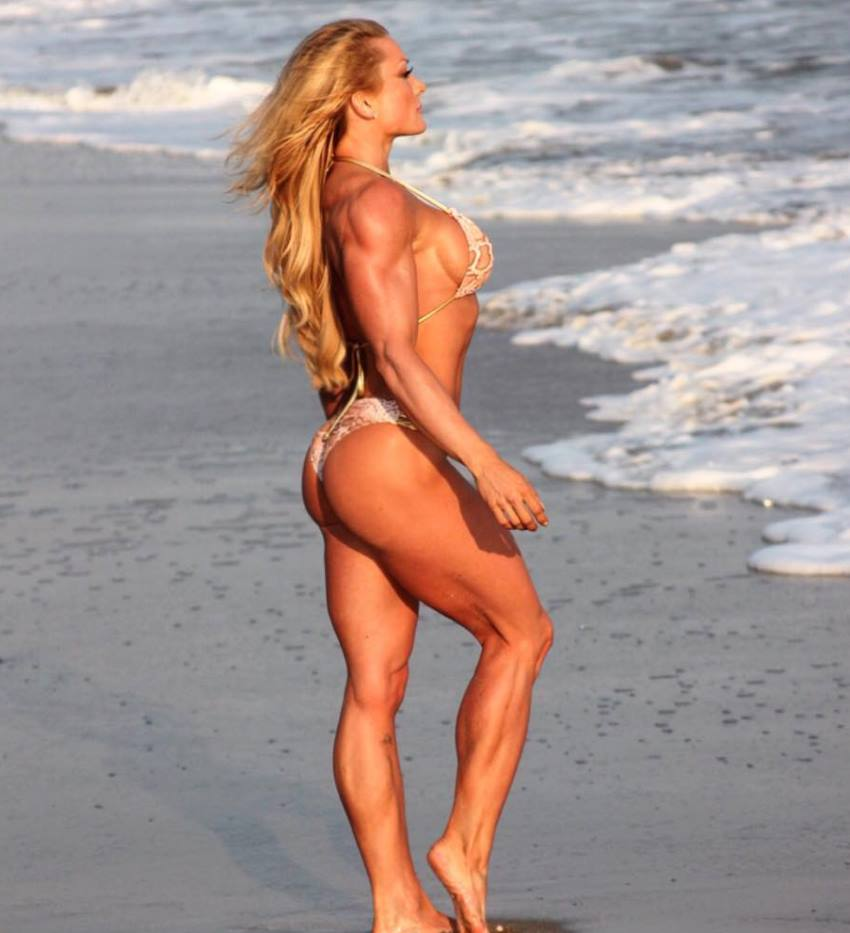Wendy Fortino in a bikini standing at a beach, looking into the distance and showing her awesome legs and arms from the side