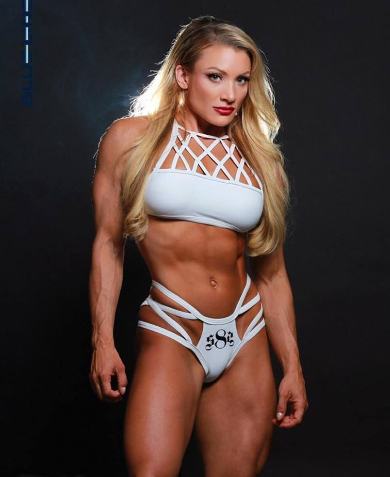 Wendy Fortino in white undie and bra, flexing her abs at the camera