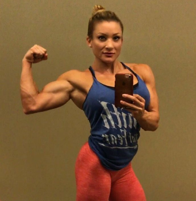 Wendy Fortino taking a selfie in blue tank top as she flexes her biceps