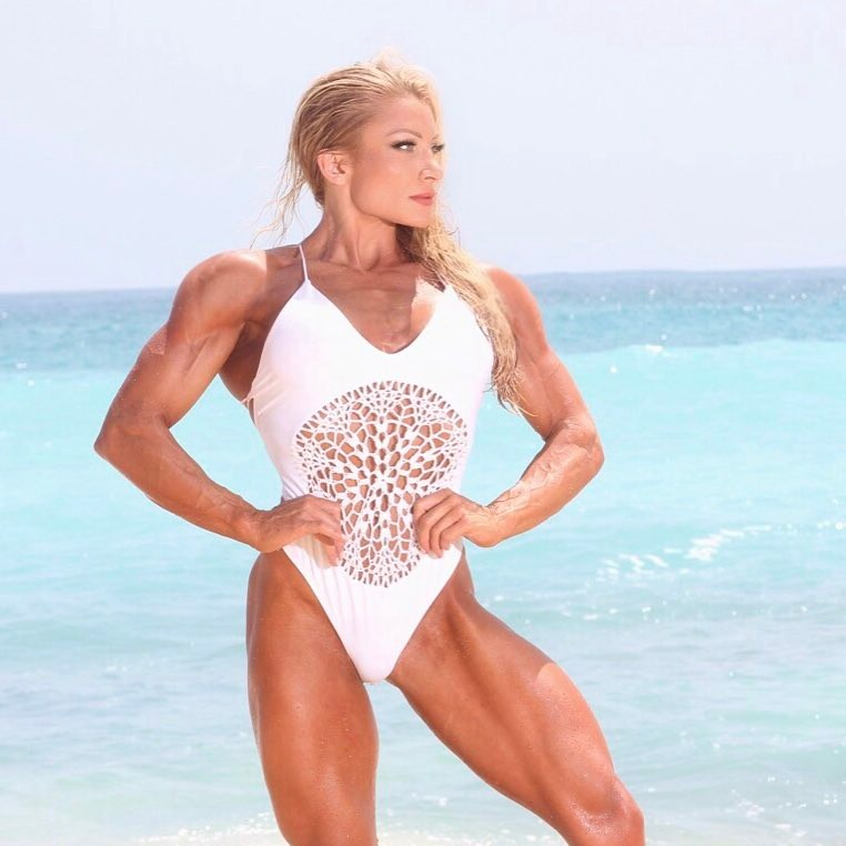 Wendy Fortino flexing her arms, lats, and legs on a beach as she looks on the right side