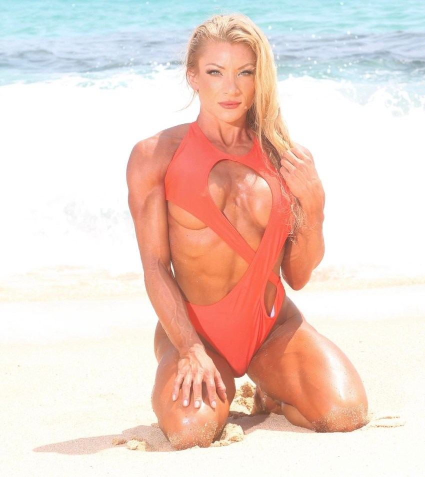 Wendy Fortino kneeling on a beach in a revealing red swimsuit, displaying her lean body