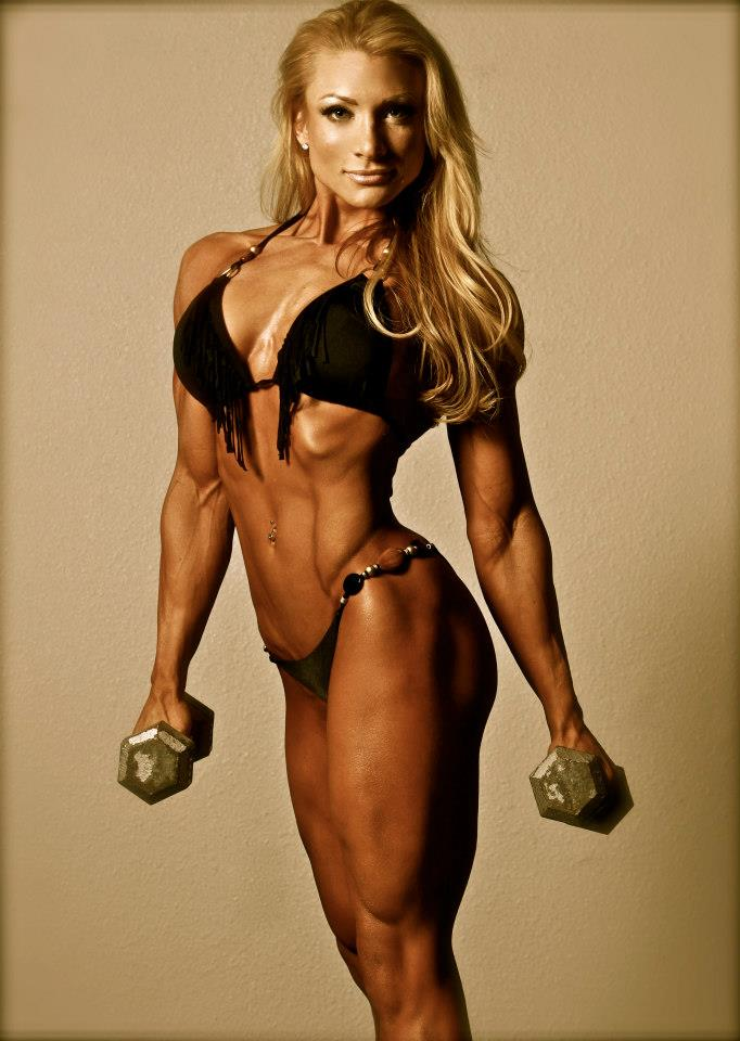 Wendy Fortino in a black biniki suit, holding dumbbells, showing her ripped body