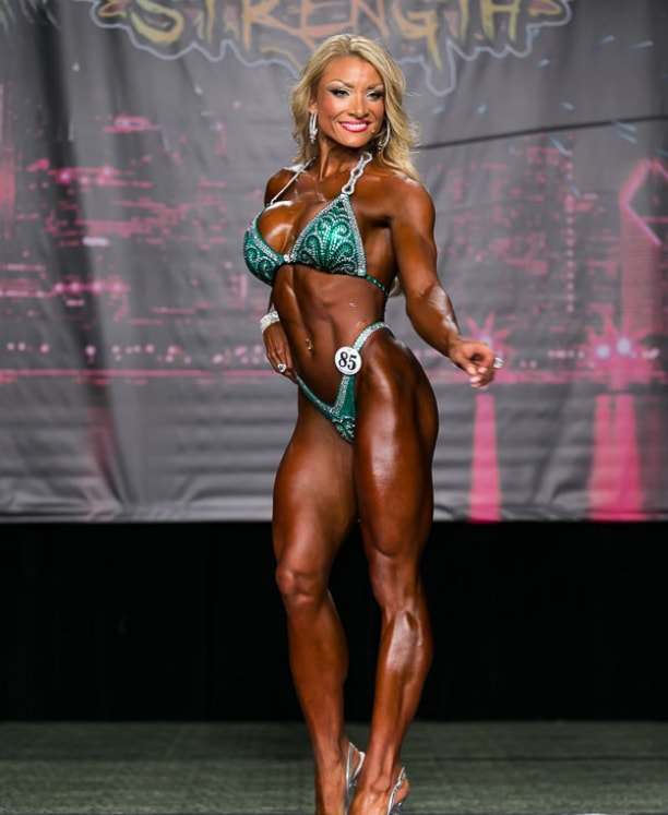 Wendy Fortino standing on a figure stage, smiling at the audience as she proudly presents her physique