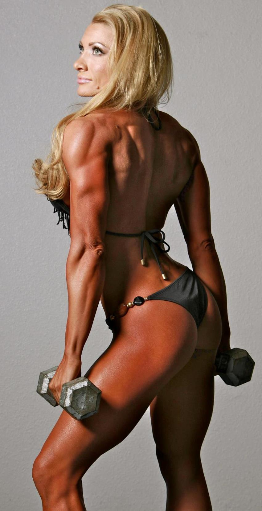 Wendy Fortino posing from the side, displaying her ripped and muscular arms and legs, as she holds dumbbells in her hands