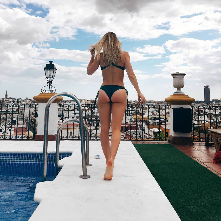 Whitney Simmons showing her toned glutes and back next to the pool