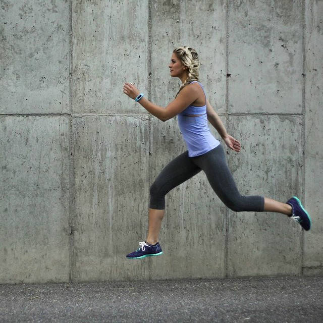 Whitney Simmons completing a jump in running gear, showing off her toned legs and arms