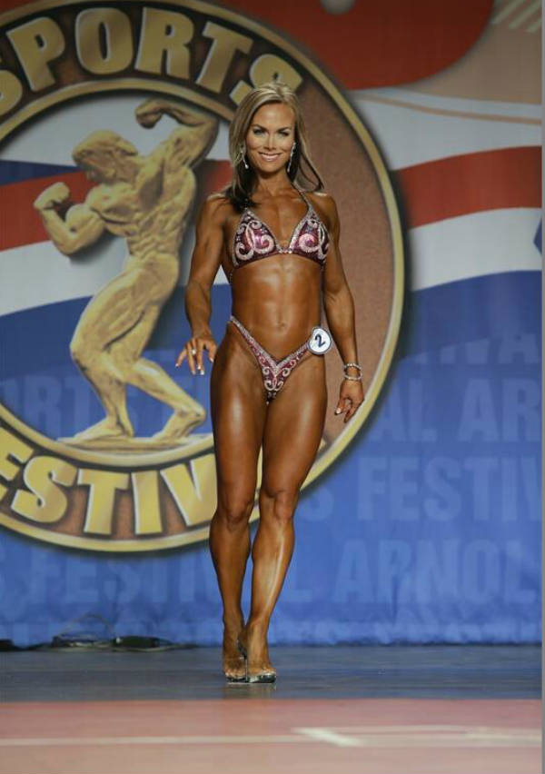 Allison Ethier posing at a competition, showing her toned abs legs and arms