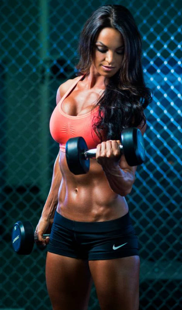 Amber Dawn Orton compelting a dumbbell lift, showing her toned abs and arms