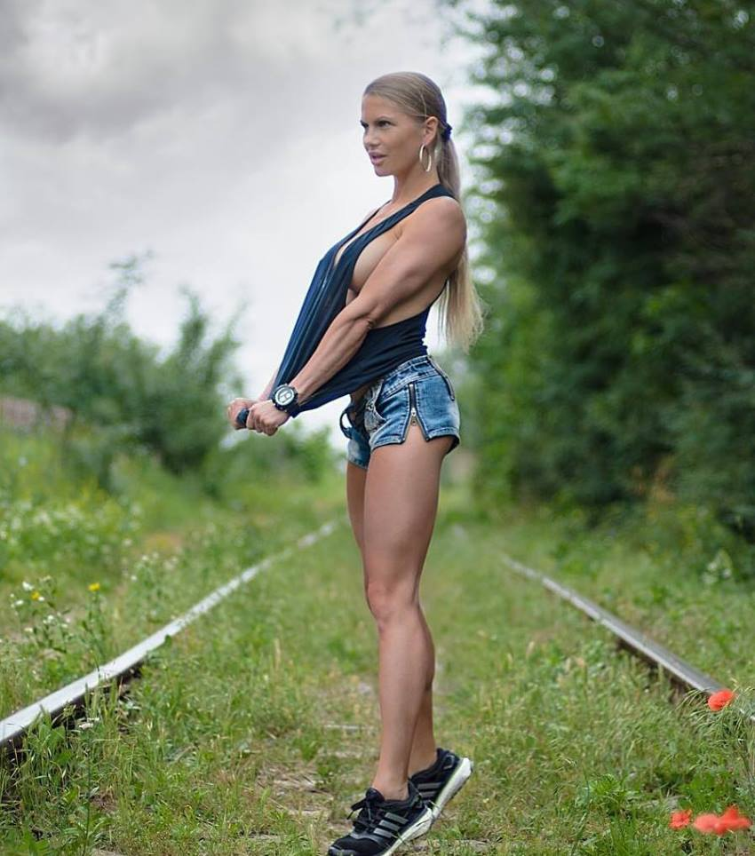 Anastasia Motorina standing on rails overgrown with grass, showcasting her awesome legs, arms, and calves