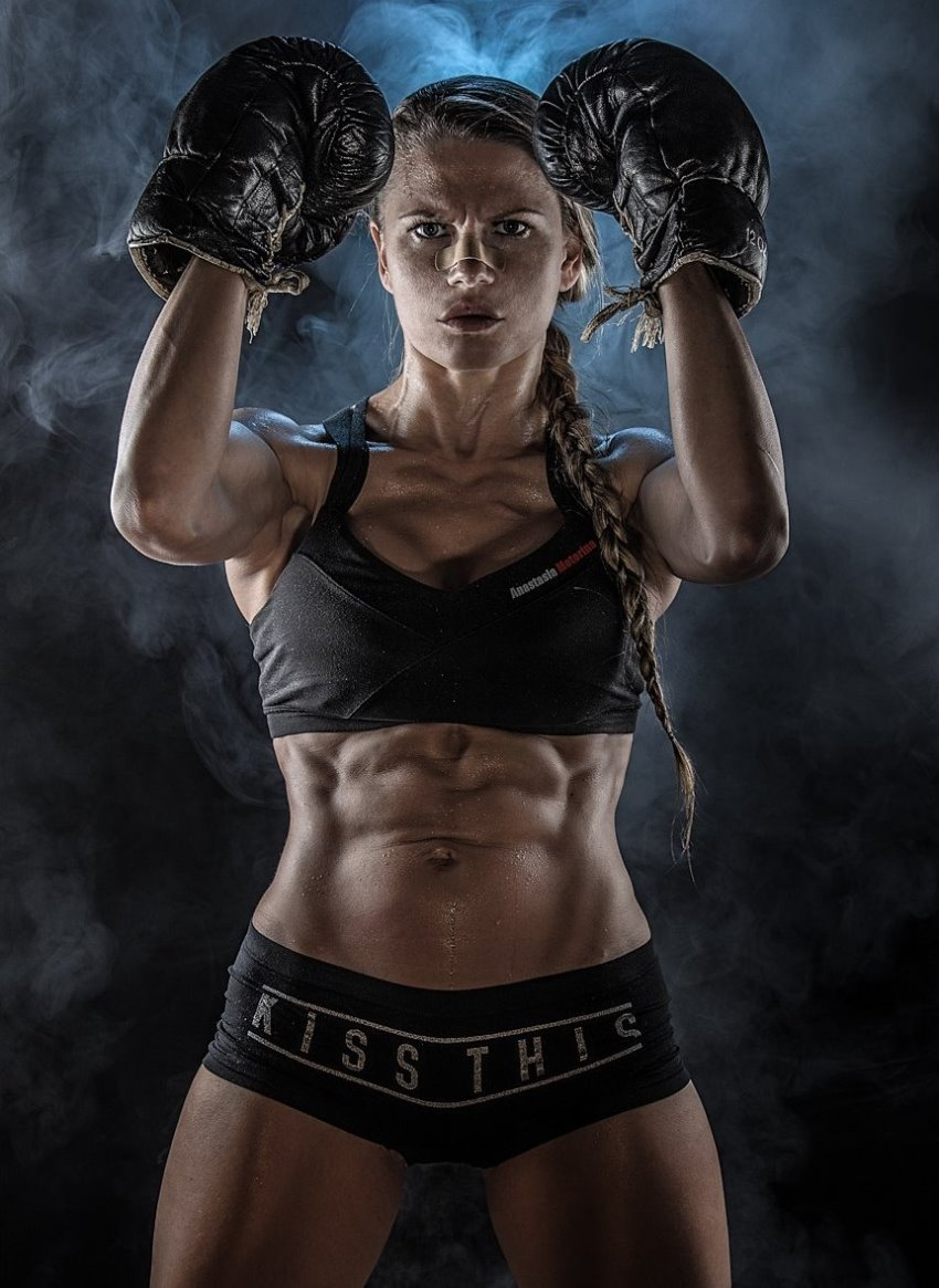 Anastasia Motorina in a fight stance, wearing boxing glowes and sportsbra, her abs looking ripped and fit