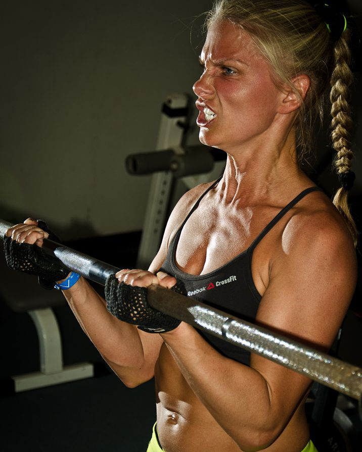 Anastasia Motorina doing barbell biceps curls with a pained grimace