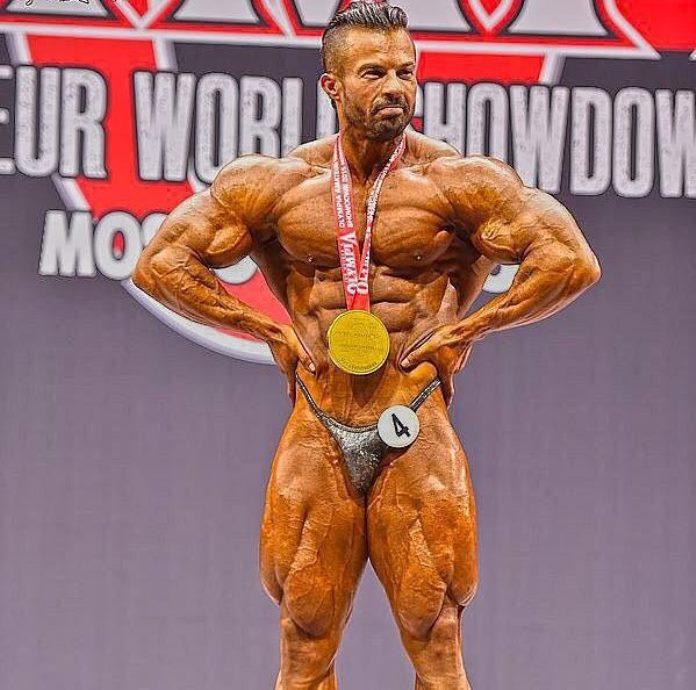 Babak Akbarniya wearing a golden medal around his neck, doing lat spread pose