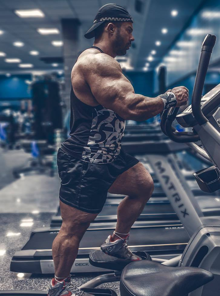 Babak Akbarniya on a treadmill machine, his arms looking massive and aesthetic from the side