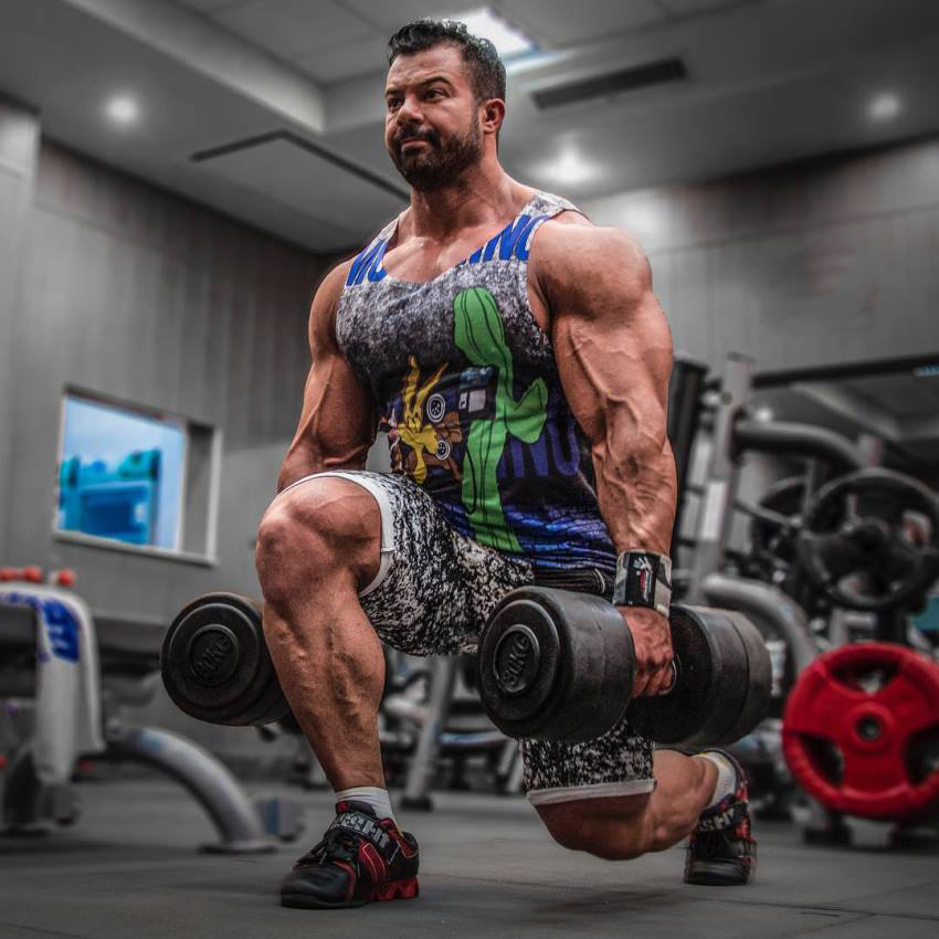 Babak Akbarniya doing lunges, his arms, shoulders, and calves looking big and ripped
