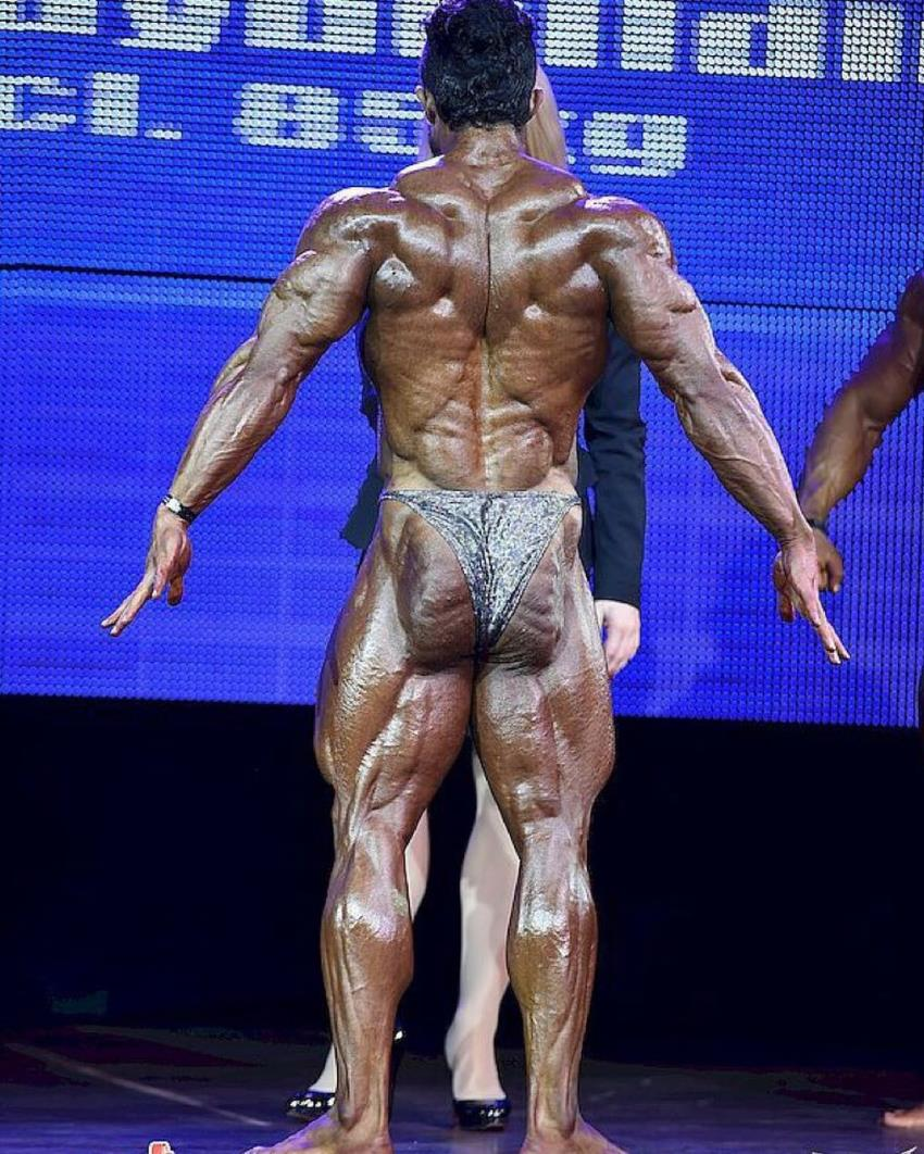 Babak Akbarniya preparing to do a back pose, his lats, traps, lower back, glutes, and legs looking incredibly ripped
