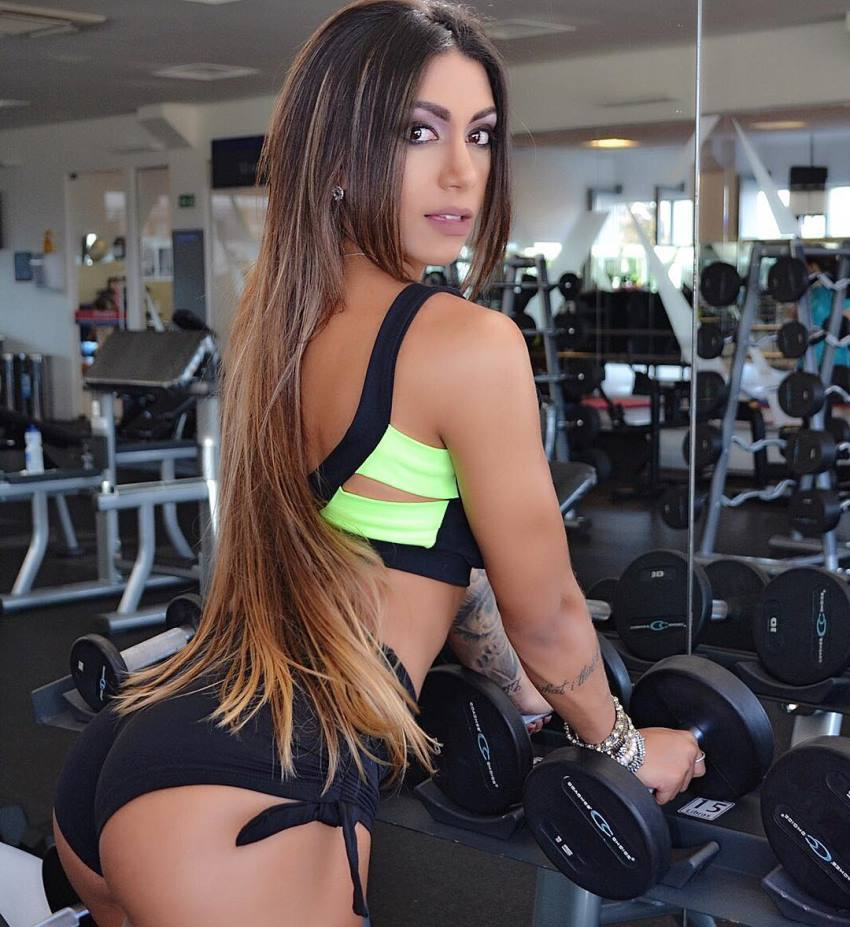 Bianca de Freitas Vitoria holding two dumbbells in a weight rack as she turns her head around at looks at the camera, showing her awesome arms and glutes