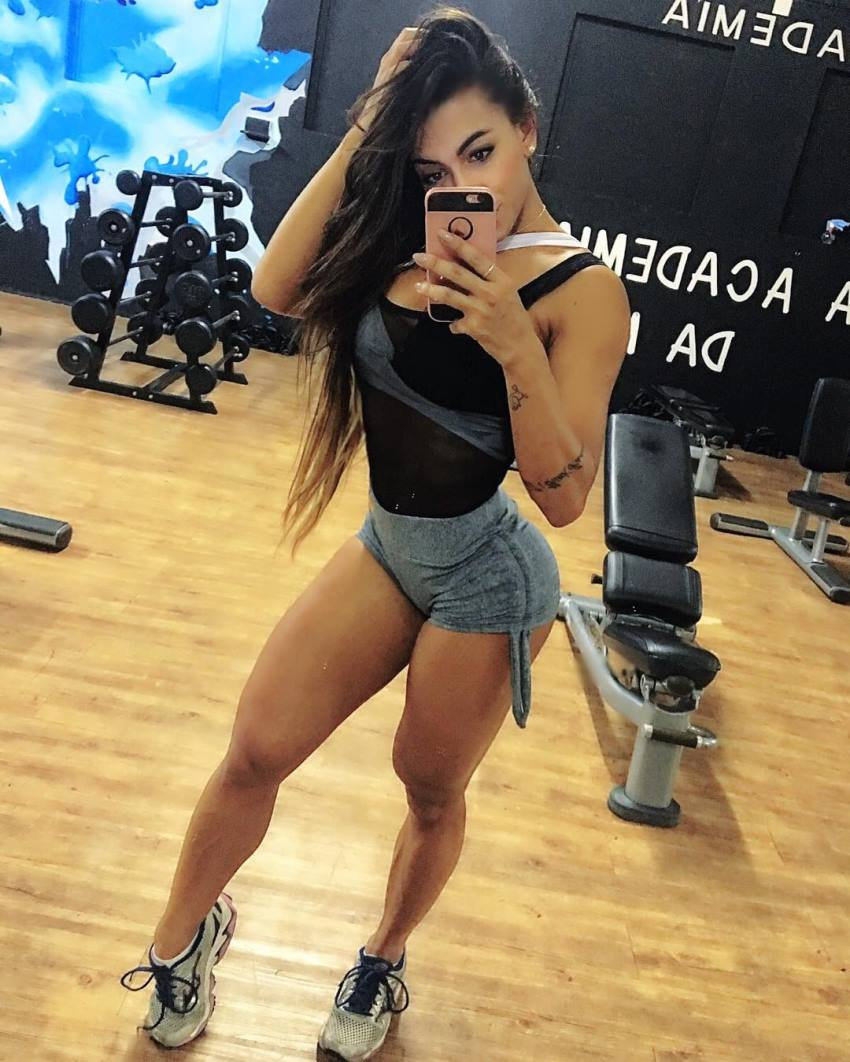 Bianca de Freitas Vitoria taking a selfie in a gym, showing off her curvy and fit legs