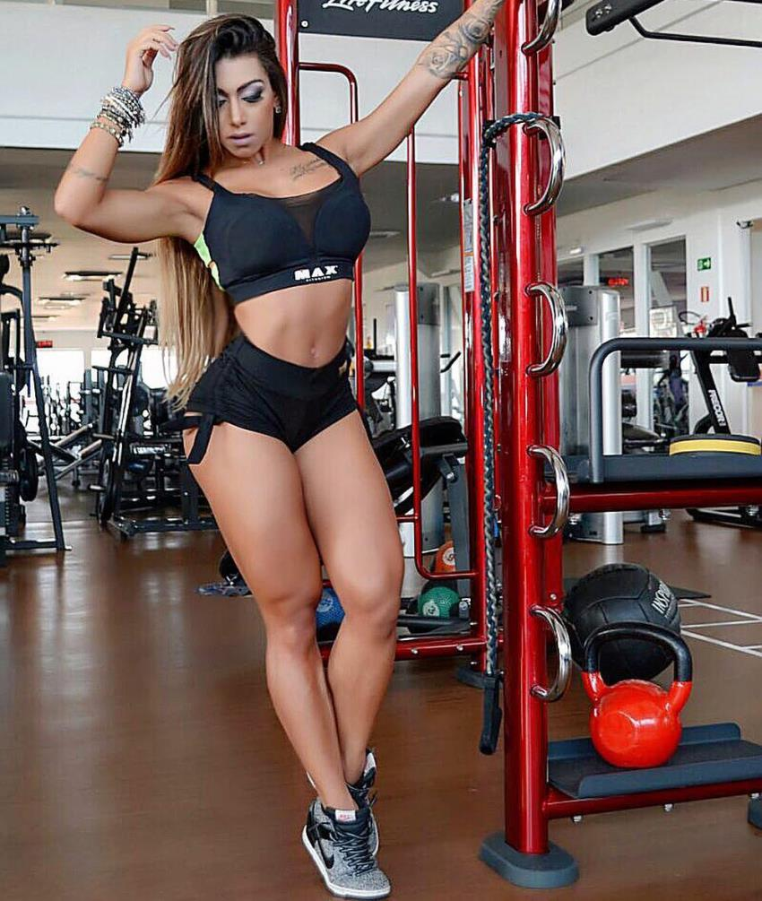 Bianca de Freitas Vitoria standing in a gym, flexing her abs and legs