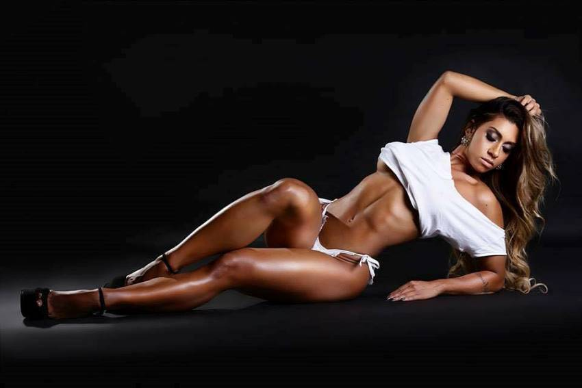 Bianca de Freitas Vitoria lying on a floor, posing for a photoshoot, looking extremely lean, fit, and aesthetic