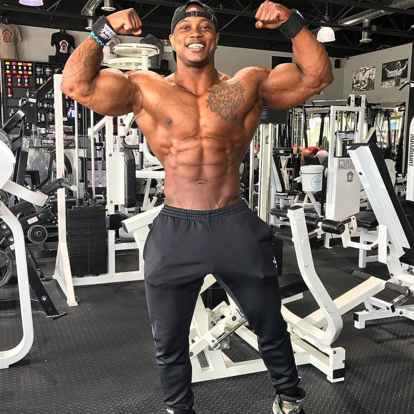 Brandon Hendrickson doing a shirtless front double biceps pose in the gym, looking muscular and lean