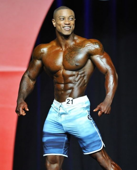 Brandon Hendrickson confidently posing on the Men's Physique Olympia stage, having a big smile on his face, as she shows his awesome and conditioned physique to the audience