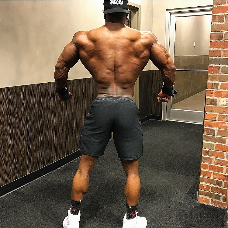 Brandon Hendrickson showing his ripped back, spreading his arms and lats
