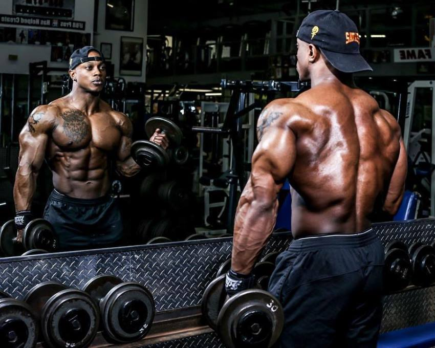 Brandon Hendrickson looking at himself in the gym mirror while doing biceps curls, looking ripped and muscular