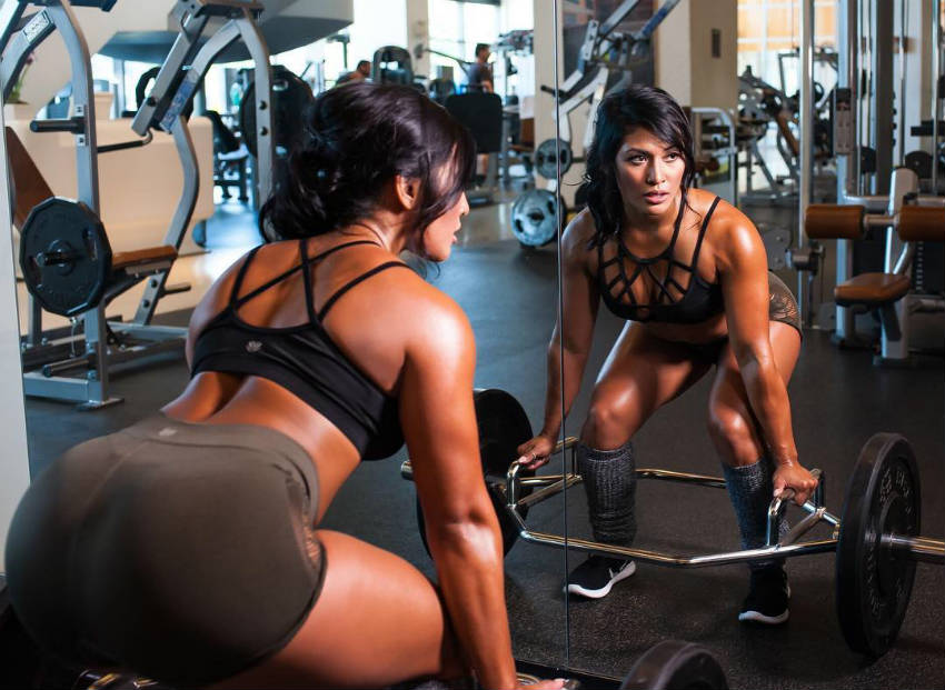 Genevieve Ava completng a deadlift, looking into the mirror and showing of her glutes and abs