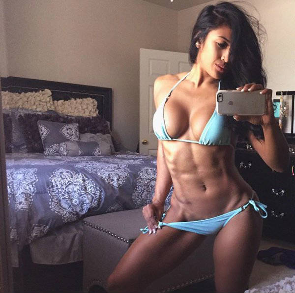 Genevieve Ava showing her toned abs and legs in bedroom shot