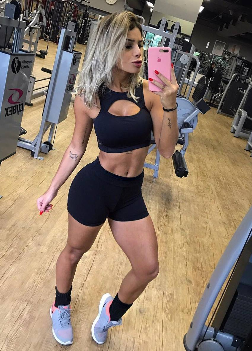 Iara Ramos taking a selfie in the gym, wearing black sportsbra and shorts, flexing her toned abs