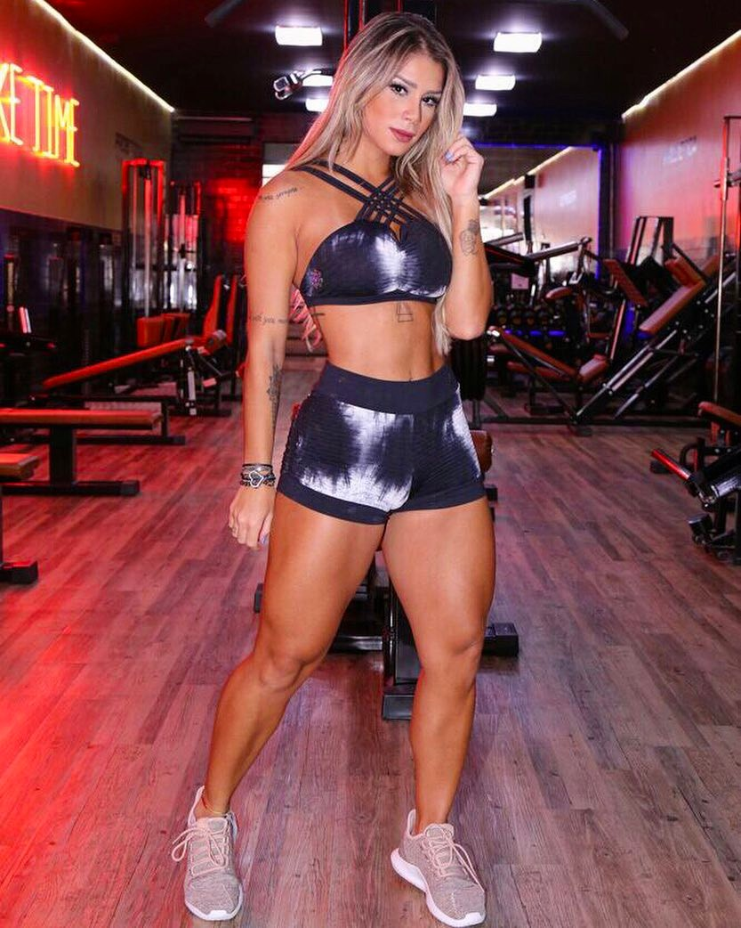 Iara Ramos standing in a gym, posing for a photo, as she shows her lean and fit legs, arms, and abs