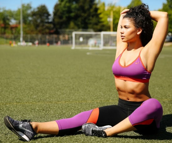 Jade Ramey sittin in a field stretching after a workout
