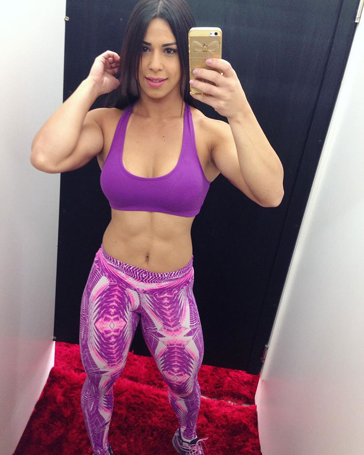 Jessica Felipe posing in the changing room mirror flexing her bulky abs