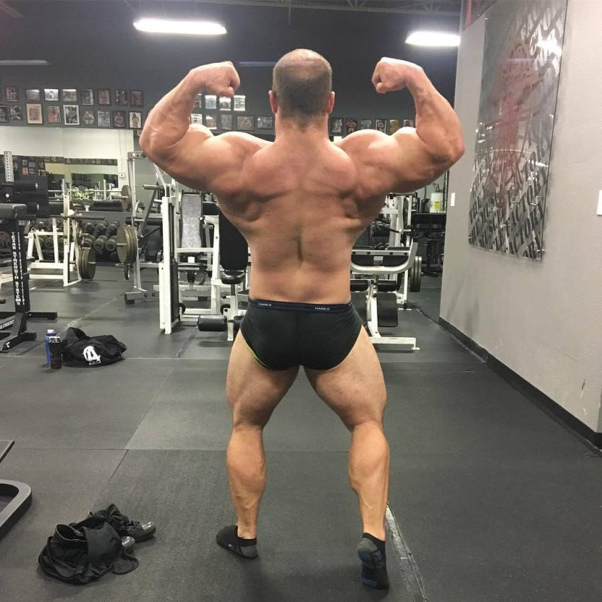 John Jewett in a shirtless back double biceps pose in the gym, looking massive