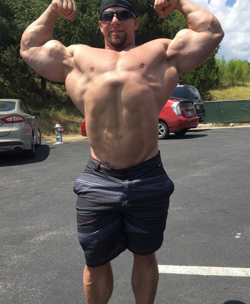 John Jewett in a shirtless front double biceps pose in an outdoor parking lot, showing his lean and big physique