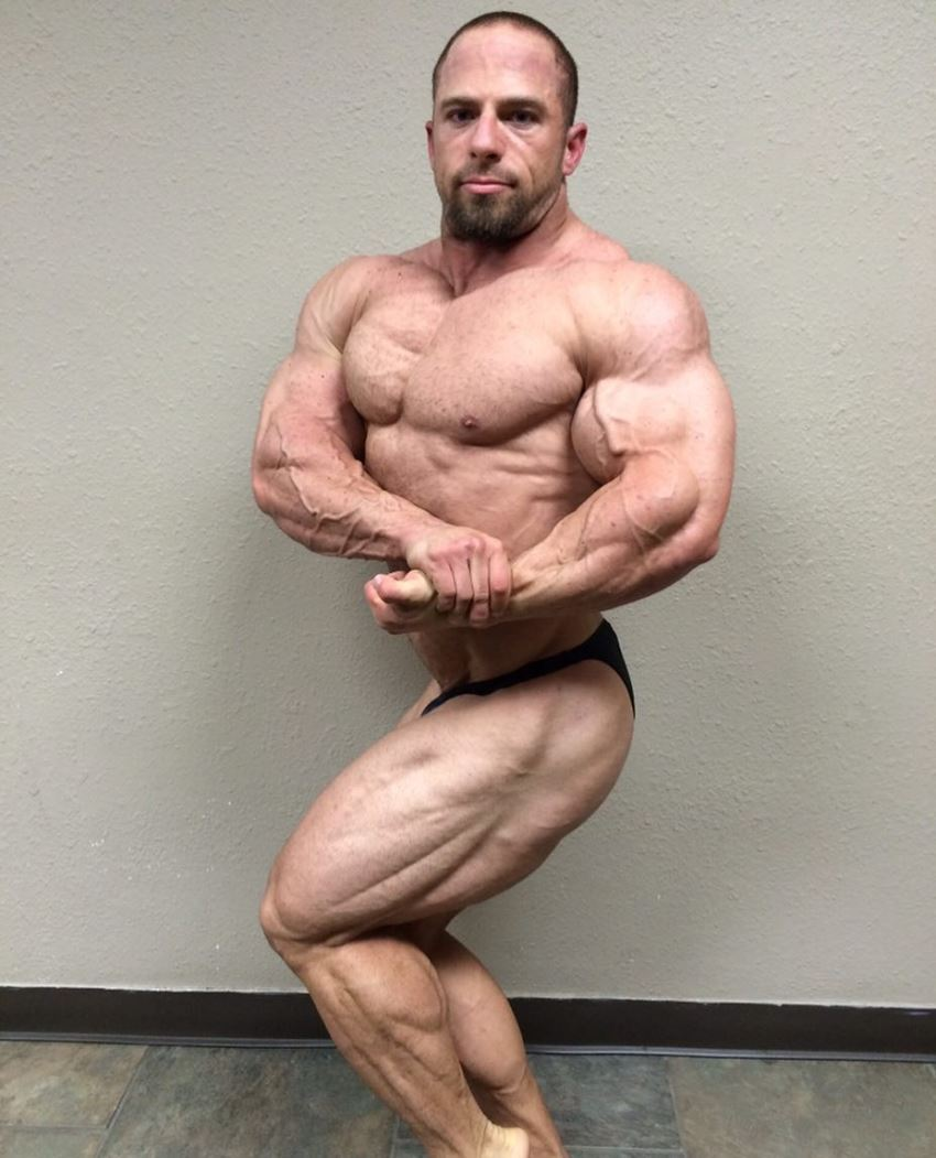 John Jewett in a side chest pose, flexing his big and aesthetic arms, legs, and chest