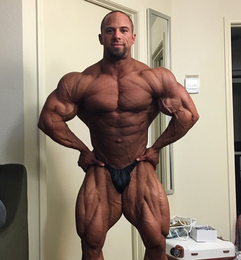 John Jewett in his room, showing his tanned-up, contest ready physique