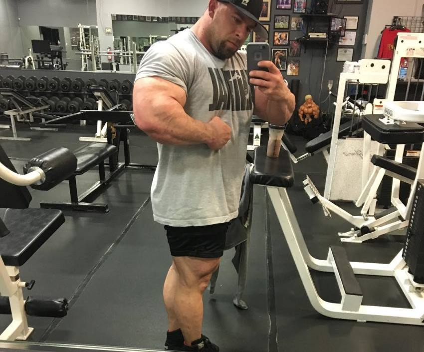 John Jewett flexing his arms while taking a selfie in the gym mirror