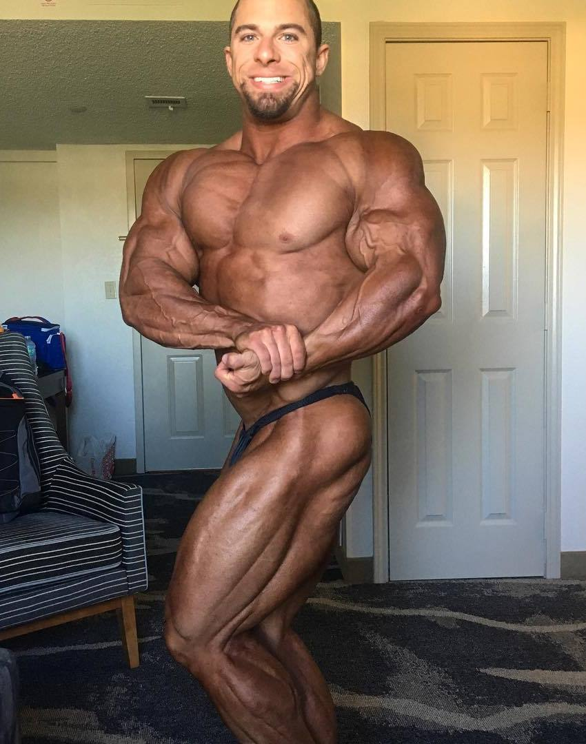 John Jewett is a side chest pose, tanned up, showing his ripped and muscular physique
