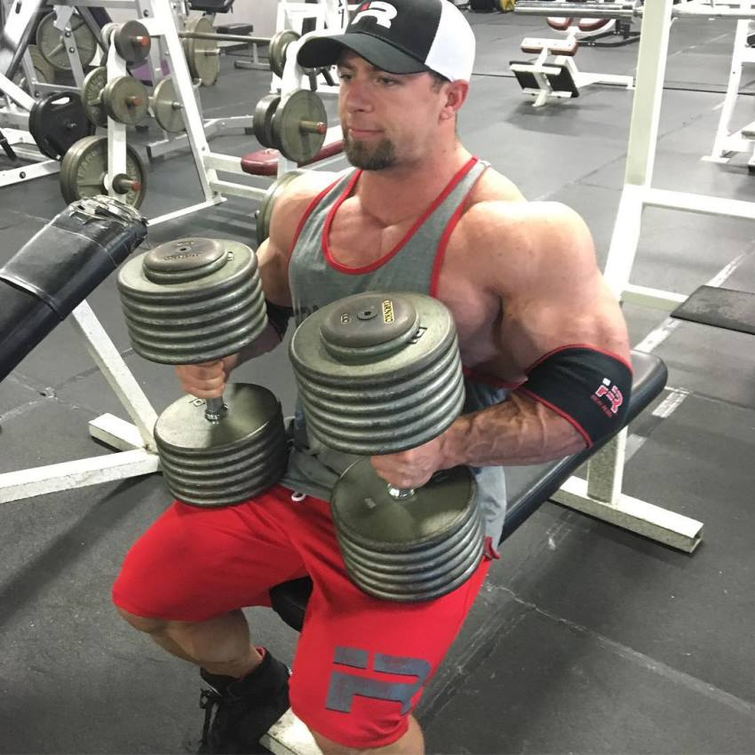 John Jewett preparing to do a heavy dumbbell bench press, looking big and muscular