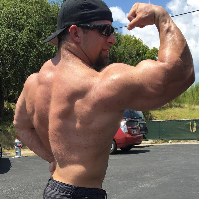 John Jewett flexing his massive biceps and back on an outdoor parking lot