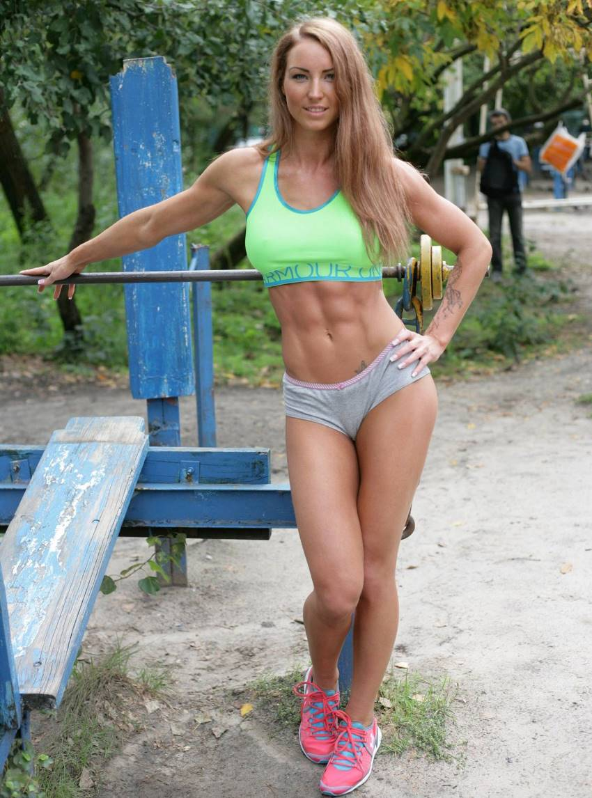 Karen Lind Thompson standing by an outdoor bench press made from wood and iron, flexing her ripped abs