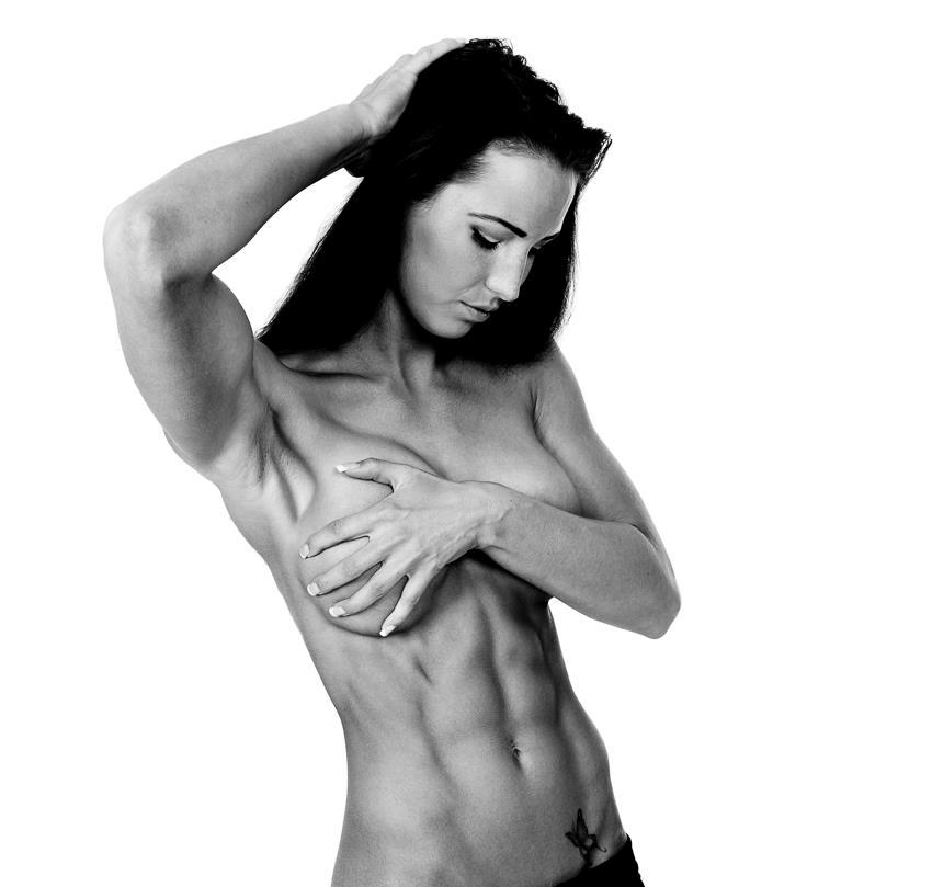 Karen Lind Thompson posing naked, covering her breasts with one of her hands, while the other one is in her hair, showing her ripped abs and obliques