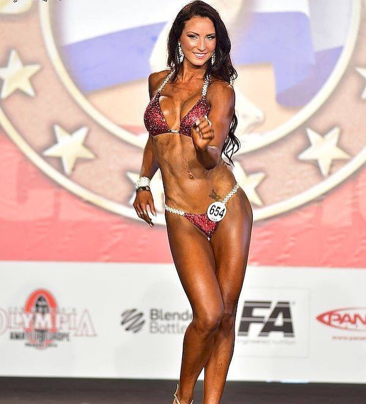 Karen Lind Thompson posing on the bikini stage, smiling at the judges, and showing her contest ready physique