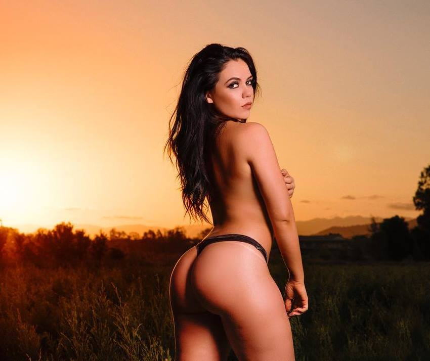 Lauryn Clare standing in a grass field with sun setting down, looking fit and curvy